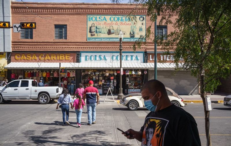 People wearing masks amid the Covid-19 pandemic are pictured on October 24, 2020 in downtown El Paso, Texas. - Businesses in the downtown district, which have always relied on shoppers from neighboring Ciudad Juárez have been impacted heavily by the ban on non-essential travel from Mexico. (Photo by Paul Ratje / AFP)