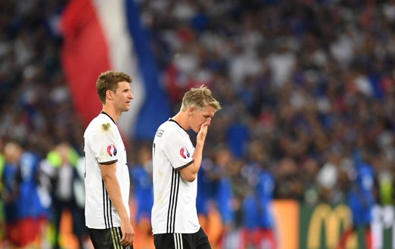 Germany's midfielder Thomas Mueller and midfielder Bastian Schweinsteiger leave the pitch after loosing 2-0 to France in the Euro 2016 semi-final football match between Germany and France at the Stade Velodrome in Marseille on July 7, 2016. France will face Portugal in the Euro 2016 finals on July 10, 2016. / AFP PHOTO / PATRIK STOLLARZ