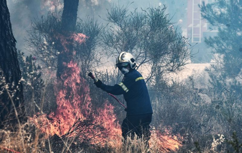 A fireman works to extinguish a forest fire at the Thessaloniki Seih Sou park, which overlooks the city of Thessaloniki, on July 13, 2021. - The risk of new fires was considered high, after several days of hot temperatures across most of Greece. (Photo by Sakis MITROLIDIS / AFP)