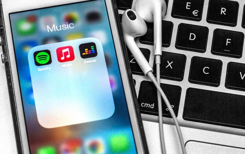 April 12, 2021, Spain: In this photo illustration a Spotify app, Apple Music app and Deezer app are seen displayed on a smartphone with headphones on a laptop keyboard.,Image: 605003859, License: Rights-managed, Restrictions: , Model Release: no, Credit line: Profimedia