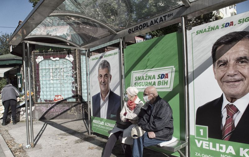 An elderly couple is sitting at a bus stop in Sarajevo, which is plastered with pre-election posters of the SDA party, otherwise known as the Bosniak Muslim Party. They are not really interested in the posters behind them.    Local elections 2020 in Bosnia and Herzegovina  These local elections come at a time of the Covid-19 pandemic, which has seen a sharp rise in the number of people infected every day in Bosnia since early October. After the heinous scandals over the procurement of medical equipment during the first wave of the pandemic in Bosnia and Herzegovina, the question is whether the voters will punish the political parties whose members were involved in the mentioned scandals. Because of Covid-19, pre-election rallies are banned or restricted with the approval of gatherings of very few people. The favorites, as always during the last 25 years since the end of the war in Bosnia, are parties with nationalist signs of the three constituent peoples in Bosnia and Herzegovina (Bosniaks, Serbs and Croats). Still, there is hope that the center's civic parties in conjunction with left-wing parties could make a surprise. We will see that after November 15, 2020. //HADROVICAHMED_1750.13176/2010211713/Credit:Ahmed Hadrovic/SIPA/2010211715,Image: 564872134, License: Rights-managed, Restrictions: , Model Release: no