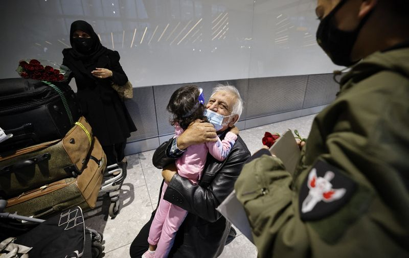 Relatives embrace as they arrive from the United States at Heathrow's Terminal 5 in west London on August 2, 2021 as quarantine restrictions ease. - People fully vaccinated in the United States and European Union, except France will now be allowed to travel to England without having to quarantine on arrival. (Photo by Tolga Akmen / AFP)