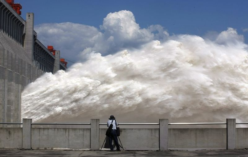 This picture taken on September 3, 2014 shows a man taking pictures of floodwater released from the Three Gorges Dam, a gigantic hydropower project on the Yangtze river, in Yichang, central China's Hubei province, after heavy downpours in the upper reaches of the dam caused the highest flood peak of the year. Eleven people died and 27 others are missing after torrential rains battered southwest China's Chongqing, a municipality in the upper reaches of the Three Gorges Dam, causing thousands of houses to collapse, state media said.    CHINA OUT     AFP PHOTO