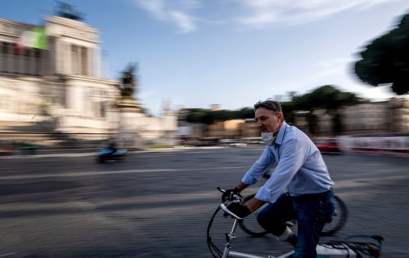 A man rides on his bicycle past the Altare della Patria monument in central Rome on May 10, 2020 during the country's partial lockdown aimed at curbing the spread of the COVID-19 infection, caused by the novel coronavirus. (Photo by Tiziana FABI / AFP)