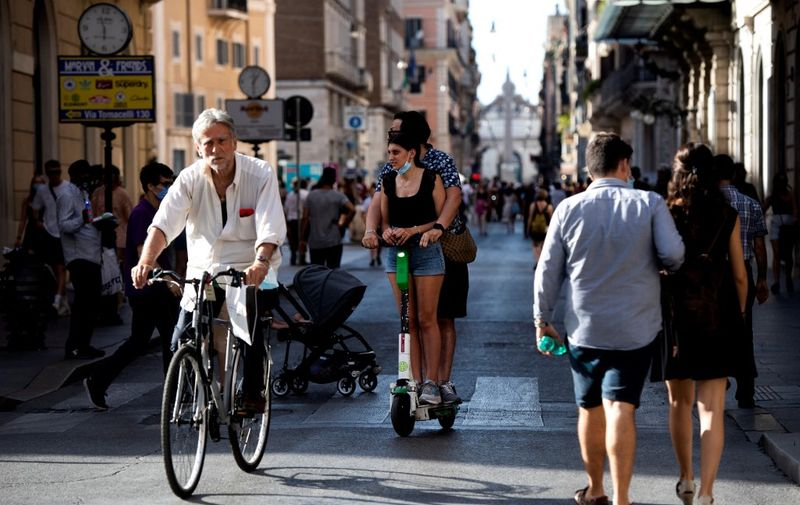 People walk and cycle along a street on the eve of Italy moving into the 'white zone' when it will not be obligatory to wear the mask outdoors in Rome on June 27, 2021. (Photo by Tiziana FABI / AFP)