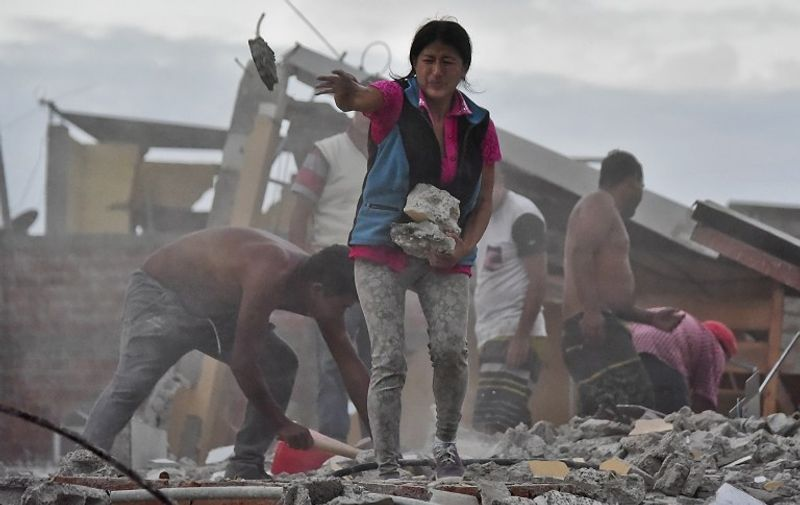 Ecuadorean Veronica Paladines, removes rubble in search for her husband at Tarqui neigbourhood in Manta, Ecuador on April 17, 2016 a day after a powerful quake hit the country. The toll from the big earthquake in Ecuador rose on Sunday to 246 dead and 2,527 people injured, the country's vice president said. / AFP PHOTO / Luis ACOSTA