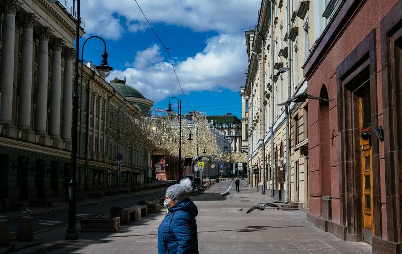 A woman walks down a deserted street in central Moscow on April 21, 2020, during a strict lockdown in Russia to stop the spread of the novel coronavirus COVID-19. (Photo by Dimitar DILKOFF / AFP)
