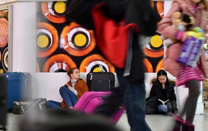 """Passengers sit with their luggage in the South Terminal building at London Gatwick Airport, south of London, on December 21, 2018, as flights started to resume following the closing of the airfield due to a drones flying. - British police were Friday considering shooting down the drone that has grounded flights and caused chaos at London's Gatwick Airport, with passengers set to face a third day of disruption. Police said it was a """"tactical option"""" after more than 50 sightings of the device near the airfield since Wednesday night when the runway was first closed. (Photo by Ben STANSALL / AFP)"""