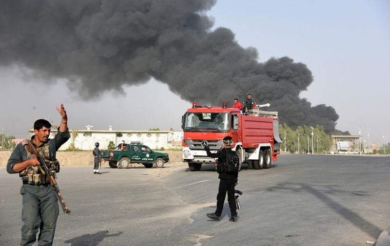 Afghan policemen arrive near a site of car bomb attack as smoke rises from the Police headquarters in Kandahar province on July 18, 2019. (Photo by JAVED TANVEER / AFP)