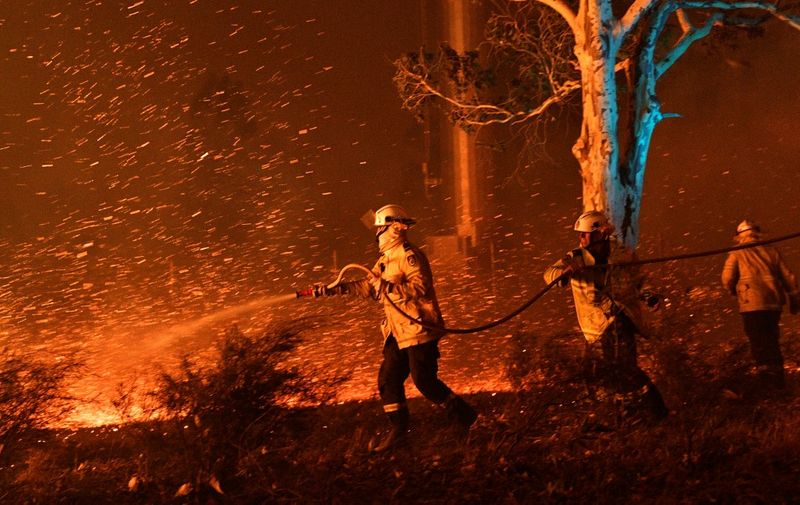 This picture taken on December 31, 2019 shows firefighters hosing down embers to secure nearby houses from bushfires near the town of Nowra in the Australian state of New South Wales. (Photo by SAEED KHAN / AFP)