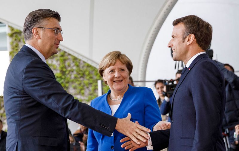 BERLIN, GERMANY - APRIL 29: German Chancellor Angela Merkel (C) and French President Emmanuel Macron (R) greet Croatian Prime Minister Andrej Plenkovic (L) upon his arrival at the Chancellery for a conference on western Balkan nations on April 29, 2019 in Berlin, Germany. German Chancellor Angela Merkel and French President Emmanuel Macron are hosting the conference that includes the leaders of North Macedonia, Albania, Croatia, Bosnia-Herzegovina, Serbia, Kosovo, Montenegro and Slovenia. (Photo by Carsten Koall/Getty Images)