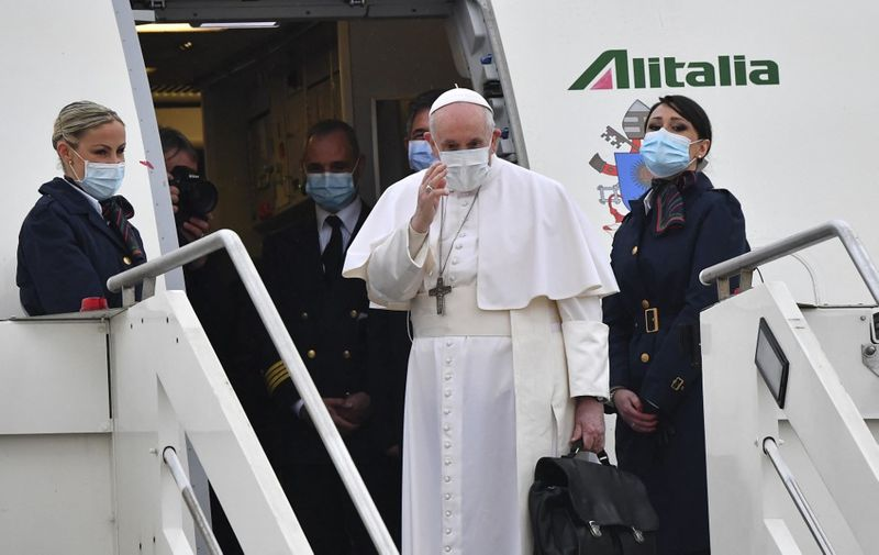 "Pope Francis waves as he boards a plane to depart to Iraq on March 5, 2021 at Rome's Fiumicino airport. - Defying security fears and the pandemic to comfort one of the world's oldest and most persecuted Christian communities, the 84-year-old pontiff starts on February 5 a 4-day visit to Iraq as a ""pilgrim of peace"", and will reach out to Shiite Muslims when he meets Iraq's top cleric, Grand Ayatollah Ali Sistani. (Photo by Andreas SOLARO / AFP)"