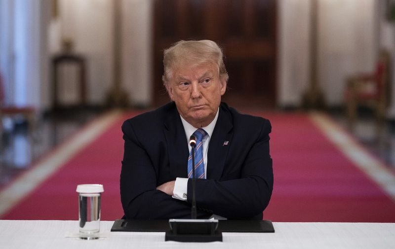 US President Donald Trump sits with his arms crossed during a roundtable discussion on the Safe Reopening of America's Schools during the coronavirus pandemic, in the East Room of the White House on July 7, 2020, in Washington, DC. (Photo by JIM WATSON / AFP)