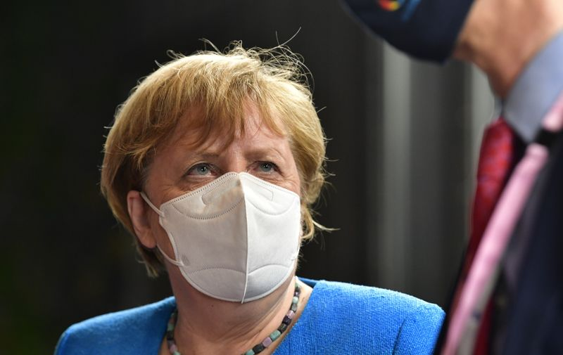 """German Chancellor Angela Merkel leaves after a meeting of an EU summit on a coronavirus recovery package at the European Council building in Brussels on July 18, 2020  An acrimonious EU summit headed into a third day on July 19 as leaders remained deadlocked over a huge post-coronavirus economic recovery plan, unable to overcome fierce resistance from the Netherlands and its """"frugal"""" allies.,Image: 544694514, License: Rights-managed, Restrictions: , Model Release: no"""