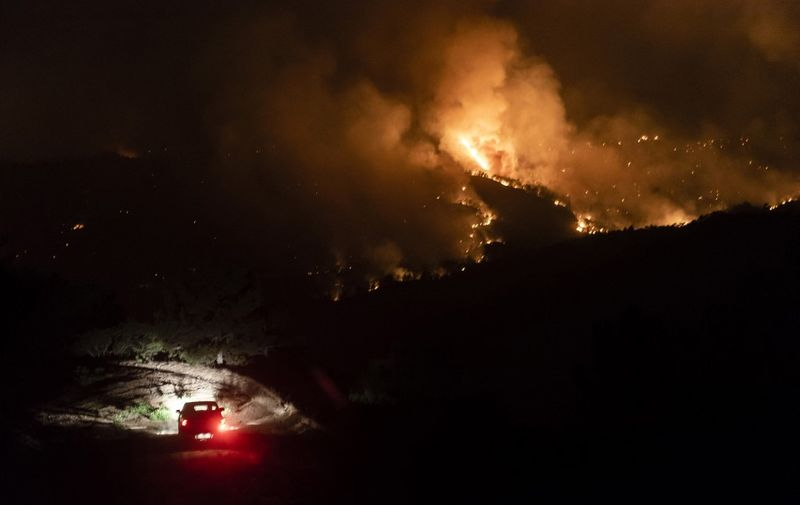A car drives on a road in the village of Vavatsinia in the Larnaca district of Cyprus, as  a giant wildfire rages on the hills above, during the night of July 3, 2021. - Cyprus yesterday requested emergency assistance of planes from Israel and the EU to fight a wildfire fanned by strong winds and high temperatures that forced the evacuation of several villages. (Photo by Iakovos Hatzistavrou / AFP)