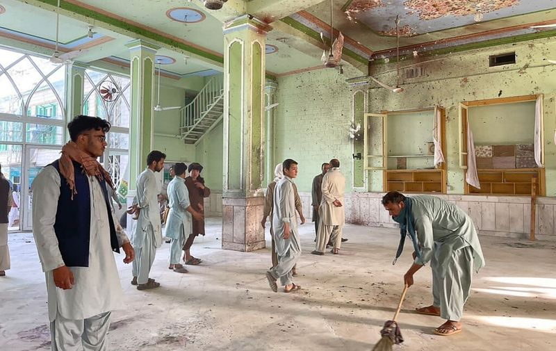Afghan men inspect the damages inside a Shiite mosque in Kandahar on October 15, 2021, after a suicide bomb attack during Friday prayers that killed at least 33 people and injured 74 others, Taliban officials said. (Photo by JAVED TANVEER / AFP)