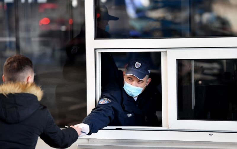 "A Serbian border police officer wearing a protective mask checks documents of a traveller on March 15, 2020, at the Batrovci border crossing between Serbia and Croatia. - Currently there are 46 positive cases of coronavirus COVID-19 in the Republic of Serbia. Serbian government temporarily prohibits the entry of foreign nationals arriving from countries particularly affected by the virus. Serbian nationals coming from the affected area go to a mandatory solitary confinement at home, under medical supervision, for 14 days. Previously indoor mass events are cancelled, and no spectators at sporting events. The government has ""temporarily closed"" 44 border crossings (the main ones remain open), to road, rail and river traffic. (Photo by Andrej ISAKOVIC / AFP)"