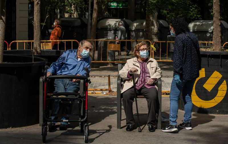 BARCELONA, SPAIN - MAY 02: An elderly man and woman wearing protective face masks sit on public benches as coronavirus lockdown restrictions eased on May 02, 2020 in Barcelona, Spain.  Spain continues to ease the Covid-19 lockdown measures this weekend, with high temperatures forecast across the country. Permitted activities now include walking with the family, outdoor exercise such as running from 6 - 10 AM and from 8 - 11 PM, going out with children from 12 - 7 PM and elderly people will be allowed to go out from 10 - 12 AM and from 7 - 8 PM. (Photo by David Ramos/Getty Images)