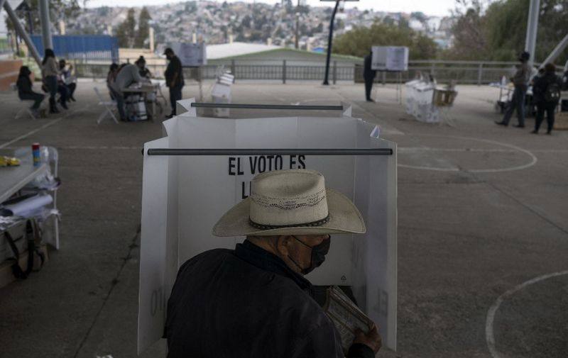 """A man casts his vote at a polling station during midterm elections in Tijuana, Mexico, on June 6, 2021. - Mexicans began voting Sunday in elections seen as pivotal to President Andres Manuel Lopez Obrador's promised """"transformation"""" of a country shaken by the coronavirus pandemic, a deep recession and drug-related violence. (Photo by Guillermo Arias / AFP)"""