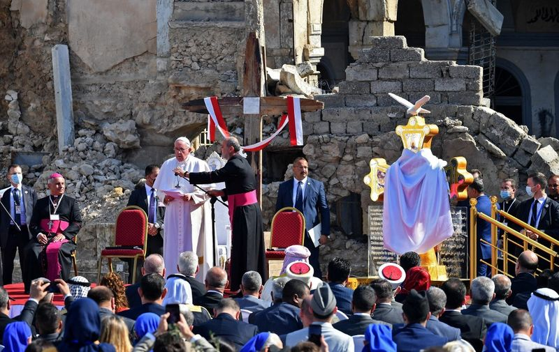 "Pope Francis (C-L) speaks at the ruins of the Syriac Catholic Church of the Immaculate Conception (al-Tahira-l-Kubra), in the old city of Iraq's northern Mosul on March 7, 2021. - Pope Francis, on his historic Iraq tour, visits today Christian communities that endured the brutality of the Islamic State group until the jihadists' ""caliphate"" was defeated three years ago (Photo by Vincenzo PINTO / AFP)"