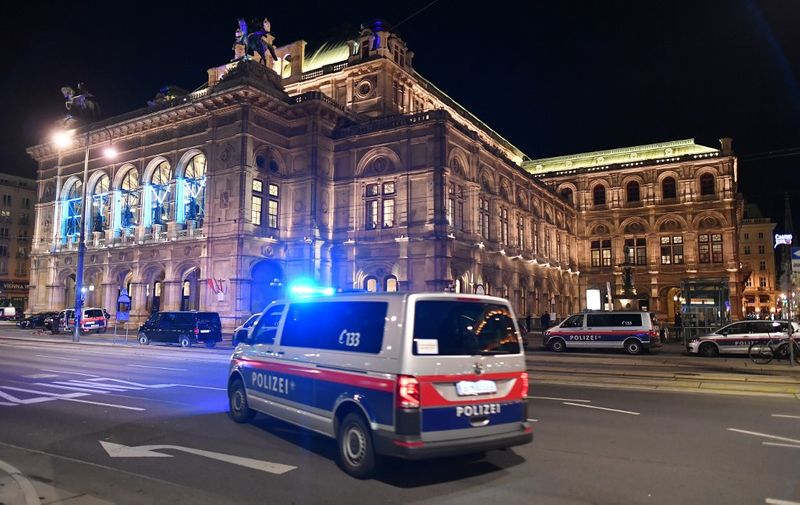 "A police car drives in front of the opera house in the center of Vienna on November 2, 2020, following a shooting. - Two people, including one attacker, have been killed in a shooting in central Vienna, police said late November 2, 2020. Vienna police said in a Twitter post there had been ""six different shooting locations"" with ""one deceased person"" and ""several injured"", as well as ""one suspect shot and killed by police officers"". (Photo by JOE KLAMAR / AFP)"