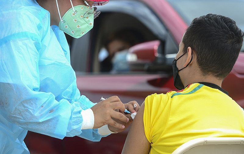 A boy receives the first dose of the Pfizer/BioNTech COVID-19 vaccine in Tegucigalpa, on September 25, 2021, during a vaccination programme for teens aged 12 to 15. (Photo by ORLANDO SIERRA / AFP)