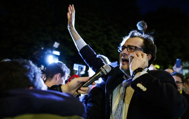 Jerome Triomphe (L) on of the two lawyers of the parents of Vincent Lambert, a quadriplegic man who has been in a vegetative state for the last decade, celebrates in the street of Paris, as he receives the news by the Paris Court of Appeal which ordered the resumption of life-support to keep the 42 years old man alive, as they take part in a white march, on May 20, 2019, in Paris from the Ministry of health to the Elysee Palace to ask for the presidential pardon for Vincent Lambert. - Doctors in France began, on May 20, 2019, removing life support for Vincent Lambert, in a hugely controversial case. The dispute over the fate of the 42 years old man, who sustained severe brain damage in a 2008 traffic accident, has split his own family and become a subject of political tensions in France. (Photo by KENZO TRIBOUILLARD / AFP)