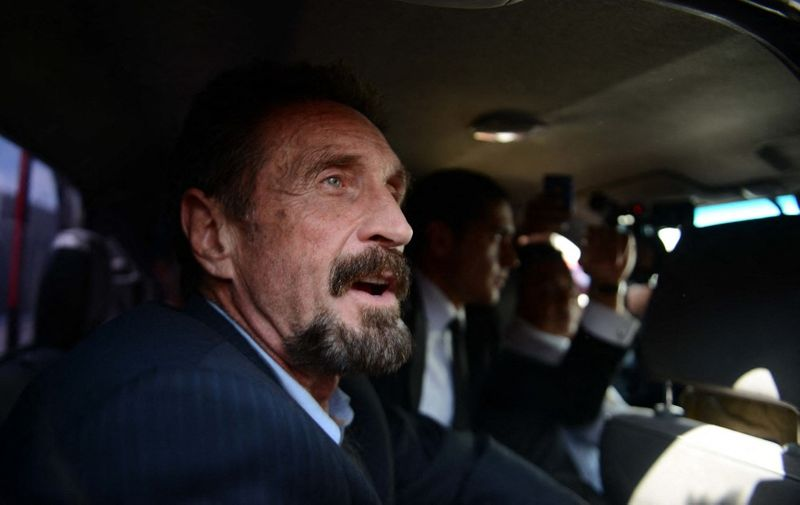US anti-virus software pioneer John McAfee gestures as he arrives at the Aurora international airport in Guatemala City on December 12, 2012. McAfee escaped immediate deportation to Belize on Wednesday as Guatemala decided to expel the American back to the United States instead.  McAfee, who entered Guatemala illegally after more than three weeks on the run, is wanted in Belize for questioning over his neighbor's murder last month.  AFP PHOTO/JOHAN ORDONEZ (Photo by JOHAN ORDONEZ / AFP)