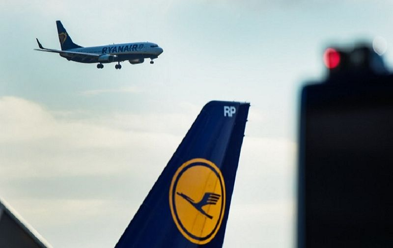 A plane of Irish low-cost airline Ryanair lands at the airport in Frankfurt am Main, western Germany, as in foreground can be seen the logo of German airline Lufthansa on November 2, 2016. Ryanair said it would base two aircraft at Frankfurt airport, Germany's busiest, serving sun-soaked tourist destinations in Portugal and Spain -- sparking outrage among German competitors. / AFP PHOTO / dpa / Andreas Arnold / Germany OUT