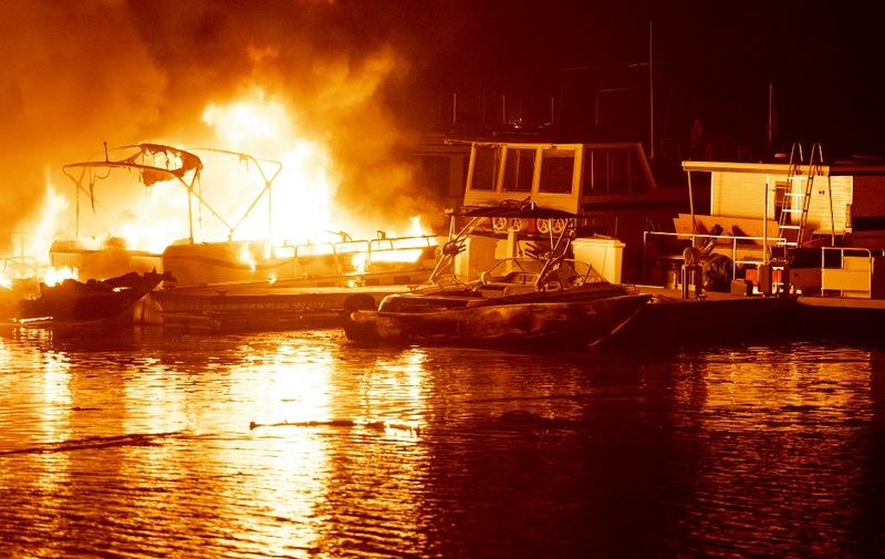 Docked boats burn on Lake Berryessa during the LNU Lightning Complex fire in Napa, California on August 19, 2020. - Thousands of people fled their homes in northern California on August 19 as hundreds of fast-moving wildfires spread across the region, burning houses and leading to the death of a helicopter pilot. (Photo by JOSH EDELSON / AFP)