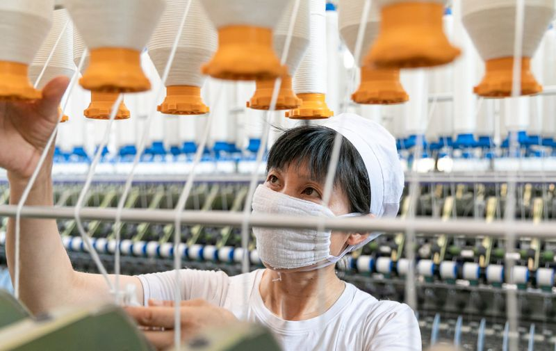 NANTONG, CHINA - JULY 15, 2021 - A worker works on a production line in a workshop of a textile company in Nantong, east China's Jiangsu Province, July 15, 2021. China's GDP grew 12.7 percent year on year in the first half of 2021.,Image: 621587829, License: Rights-managed, Restrictions: *** World Rights Except China ***, Model Release: no, Credit line: Profimedia