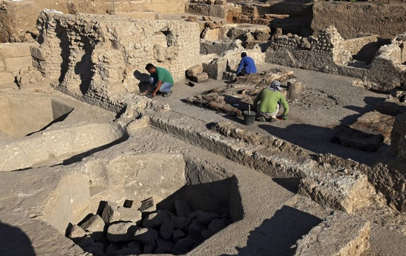"""Archaeologists and technicians of the Israel Antiquities Authority excavate inside a winepress at the Tel Yavne site in central Israel on October 11, 2021, where a massive wine production facility was discovered, the largest such complex of winepresses known from the Byzantine Period. - Israeli archaeologists on October 11 uncovered a 1,500-year-old industrial wine complex dating to the Byzantine-era, which produced some two million litres of the popular drink annually and was the world's """"largest"""" such centre at the time. The facility in Yavne, a city south of Tel Aviv that was a Jewish settlement during biblical times and a key city after the destruction of Jerusalem in 70 AD, is comprised of five wine presses sprawling over a square kilometre. (Photo by MENAHEM KAHANA / AFP)"""