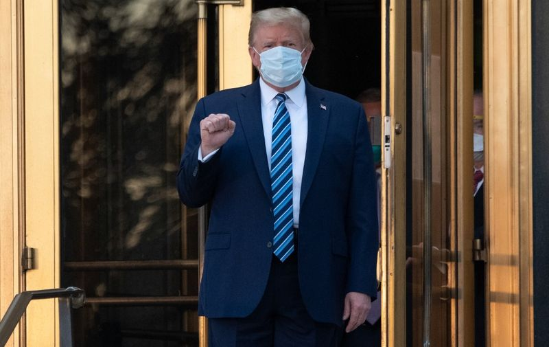 "US President Donald Trump walks out of Walter Reed Medical Center in Bethesda, Maryland before heading to Marine One on October 5, 2020, to return to the White House after being discharged. - Trump announced he would be ""back on the campaign trail soon"", just before returning to the White House from a hospital where he was being treated for Covid-19. (Photo by SAUL LOEB / AFP)"