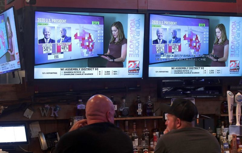 JANESVILLE, WISCONSIN - NOVEMBER 03: Patrons at the Whiskey Ranch Bar and Grill watch as election returns are broadcast on November 03, 2020 in Janesville, Wisconsin. After a record-breaking early voting turnout, Americans went to the polls on the last day to cast their vote for incumbent U.S. President Donald Trump or Democratic nominee Joe Biden in the 2020 presidential election.   Scott Olson/Getty Images/AFP
