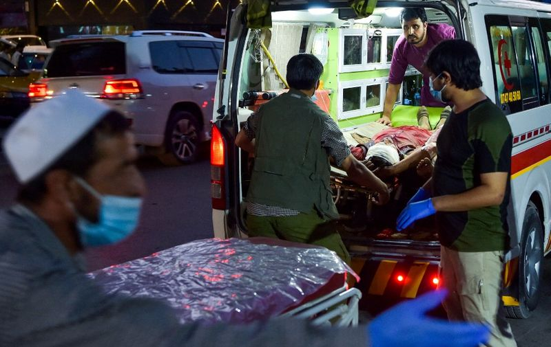 EDITORS NOTE: Graphic content / Medical staff bring an injured man to a hospital in an ambulance after two powerful explosions, which killed at least six people, outside the airport in Kabul on August 26, 2021. (Photo by Wakil KOHSAR / AFP)