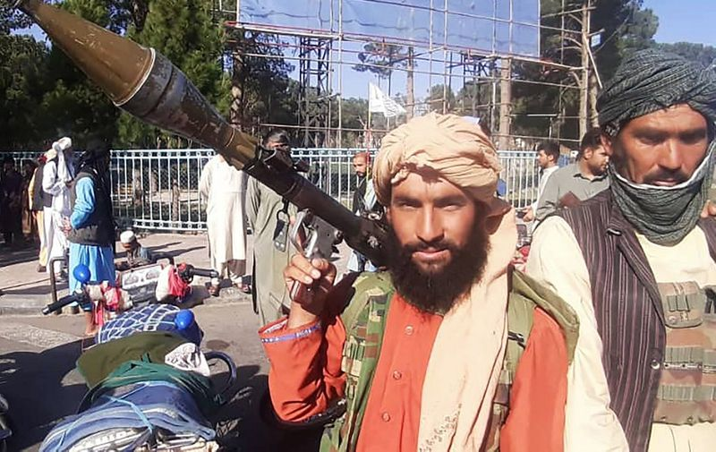 In this picture taken on August 13, 2021, a Taliban fighter holds a rocket-propelled grenade (RPG) along the roadside in Herat, Afghanistan's third biggest city, after government forces pulled out the day before following weeks of being under siege. (Photo by - / AFP)