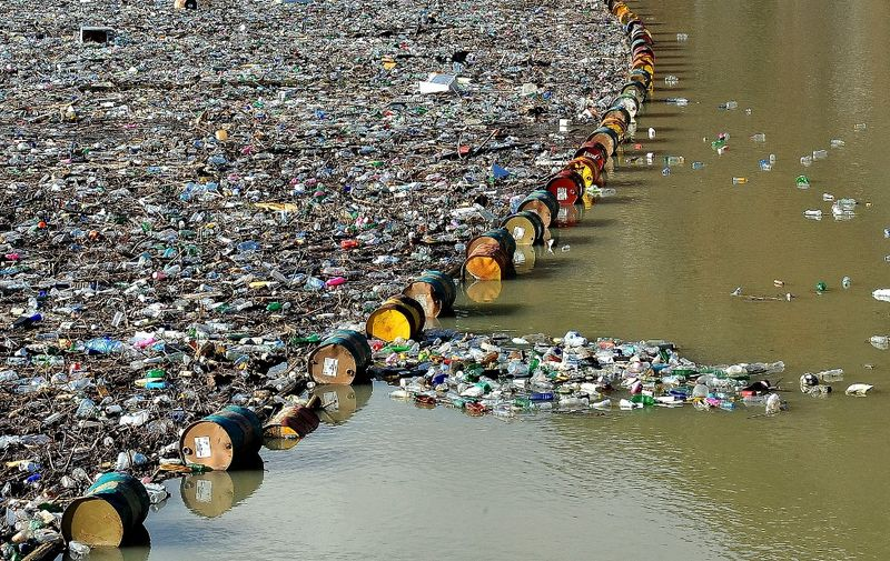 """More than 5,000 cubic meters of waste and debris are seen at the dam of """"Visegrad"""" water power plant, on river Drina, near Eastern-Bosnian town of Visegrad, on January 5, 2021. - Tons of waste that have been inappropriately disposed on unregulated dump sites, in communities along upper flow of river Drina and it's tributaries, have been flushed by the rivers, as water levels raised in previous days due to increased amount of rain. Build up of the waste and debris threatens normal operation of """"Visegrad"""" dam and puts at risk normal operation on further two power plants in lower flow of the Drina river. (Photo by ELVIS BARUKCIC / AFP)"""
