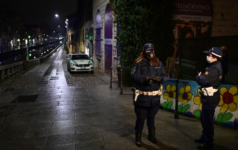 Police officers make a round in the Navigli district in southern Milan on October 22, 2020, during the closing of the bars and restaurants. - Lombardy region imposes a nighttime virus curfew from 11:00 pm until 5:00 am. (Photo by Miguel MEDINA / AFP)
