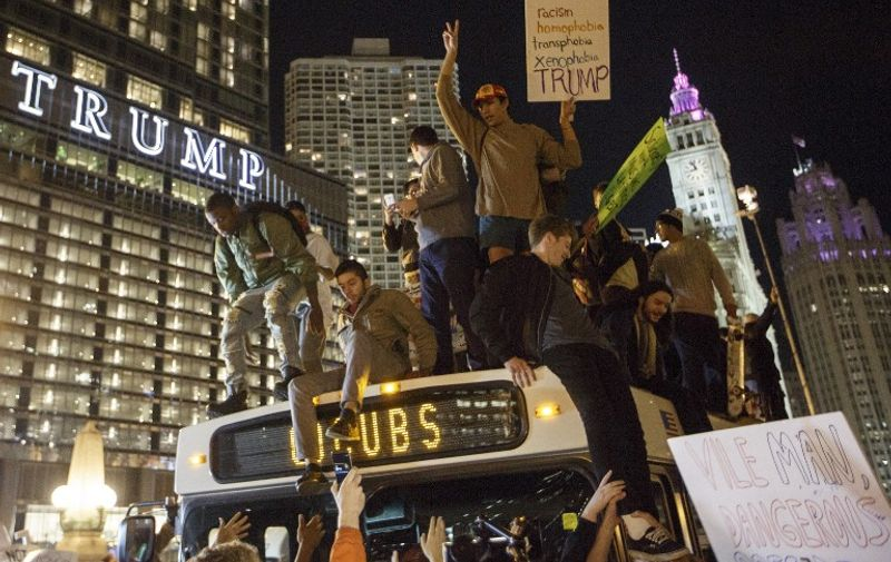 CHICAGO, IL - NOVEMBER 09: Demostrators protest on top of a bus outside of the Trump Tower November 9, 2016 in Chicago, Illinois. Thousands of people in several cities across the country took to the streets a day after Donald Trump was elected president.   John Gress/Getty Images/AFP
