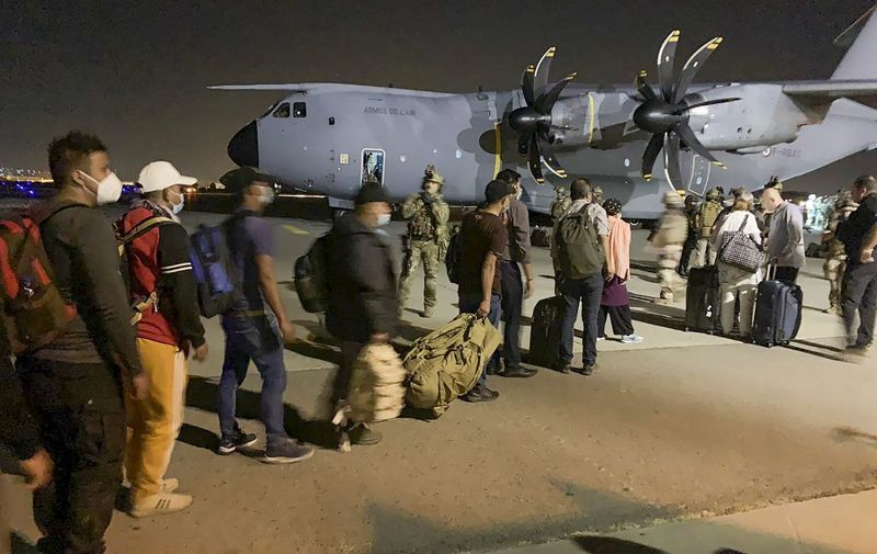 People line up to board a French military transport plane at the Kabul airport on August 17, 2021, for evacuation from Afghanistan after the Taliban's stunning military takeover of the country. (Photo by STR / AFP)