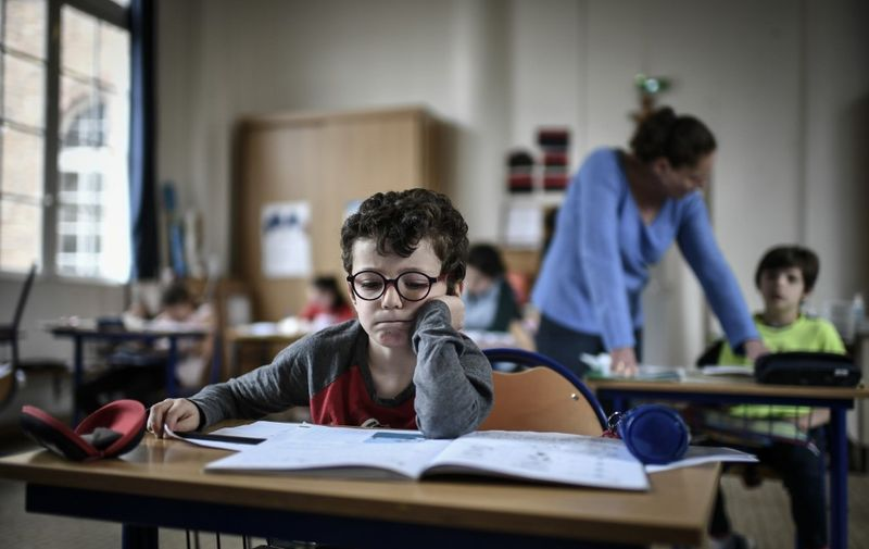 A child of medical staff member read in the classroom at the Eugene Napoleon Saint-Pierre Fourier private school on April 30, 2020, in Paris, on the 45th day of a strict lockdown in France to stop the spread of COVID-19 (novel coronavirus). (Photo by STEPHANE DE SAKUTIN / AFP)