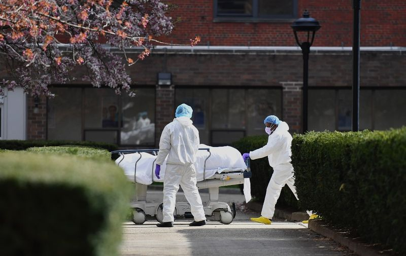 """Medical personnel wearing personal protective equipment transport the body of a deceased patient from a refrigerated truck to Kingsbrook Jewish Medical Center on April 8, 2020 in Brooklyn, New York. - New York state has recorded its highest number of COVID-19 deaths in 24 hours, Governor Andrew Cuomo said on April 7, adding though that hospitalizations appeared to be """"plateauing."""" (Photo by Angela Weiss / AFP)"""