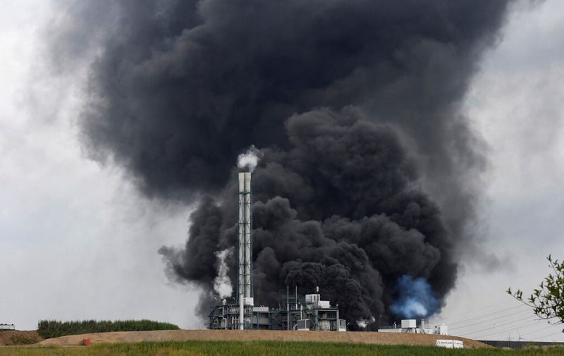 Smoke rises from a landfill and waste incineration area at the Chempark industrial park run by operator Currenta following an explosion in Leverkusen's Buerrig district, western Germany, on July 27, 2021. - At least 16 people were injured and five missing after an explosion at the chemical park in Leverkusen, western Germany, that sent a huge column of black smoke into the air, officials said, urging residents to stay indoors. (Photo by Roberto Pfeil / AFP)