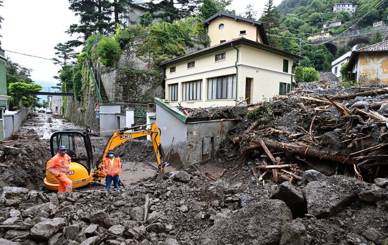 Workers stand by an excavator used to clear the damages caused by a landslide in Laglio after heavy rain caused floods in towns surrounding Lake Como in northern Italy, on July 28, 2021. (Photo by MIGUEL MEDINA / AFP)