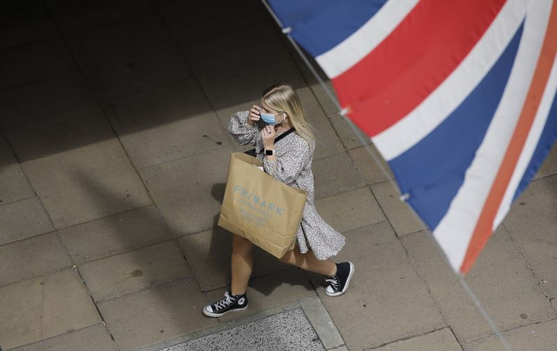 A shopper wears a face mask on Oxford Street om London on July 24, 2020, after wearing facemasks in shops and supermarkets became compulsory in England as a measure to combat the spread of the novel coronavirus. (Photo by Tolga AKMEN / AFP)