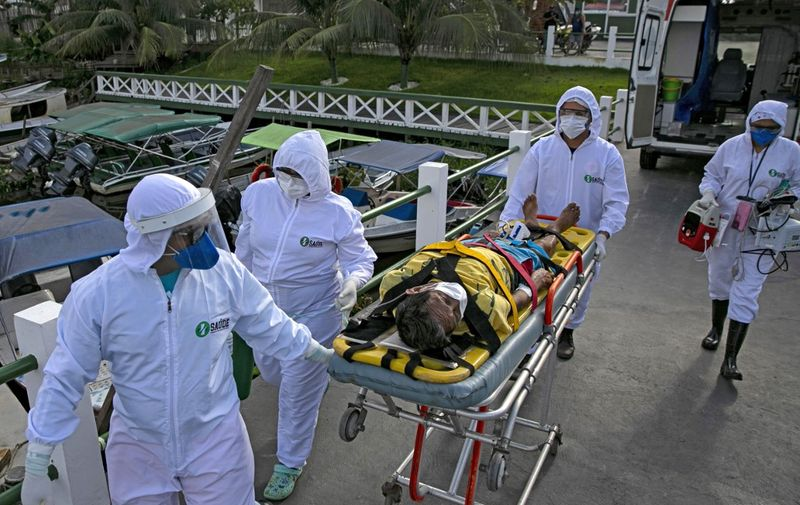Health personnel of a medical emergency response service carry Brazilian Eladio Lopes, 79, -infected with the new coronavirus- on a stretcher to be transferred on an ambulance boat from the community of Portel to a hospital in Breves, on Marajo island, Para state, Brazil, on May 25, 2020. - Ambulance boat services allow critical COVID-19 patients to be tranferred in very remote areas surrounded by water in Brazil. (Photo by TARSO SARRAF / AFP)
