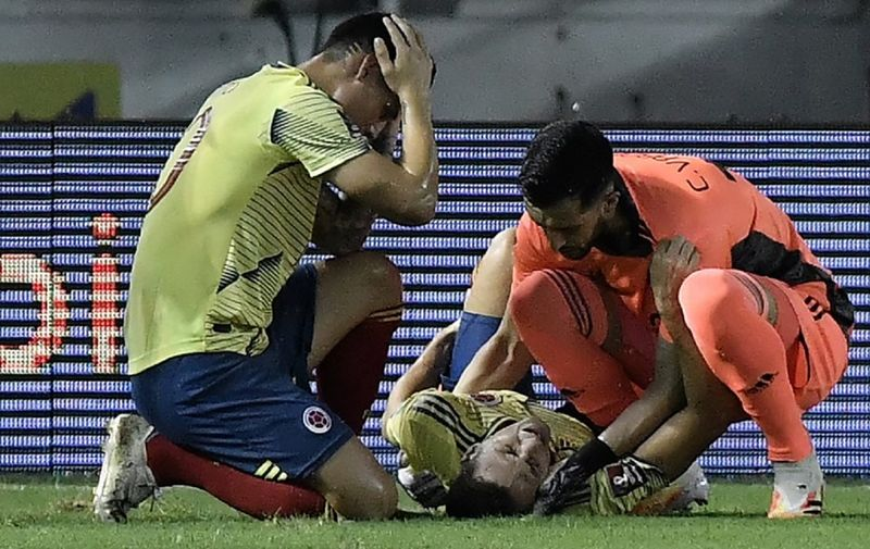 Colombia's Santiago Arias lies injured during the 2022 FIFA World Cup South American qualifier football match against Venezuela at the Roberto Melendez Metropolitan Stadium in Barranquilla, Colombia, on October 9, 2020, amid the COVID-19 novel coronavirus pandemic. (Photo by Gabriel Aponte / POOL / AFP)