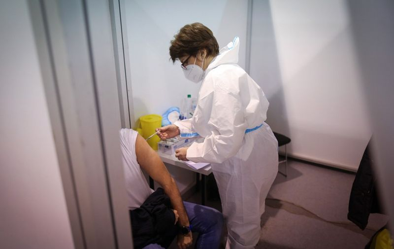 A man receives a dose of a Covid-19 vaccine in Belgrade Fair turned into a vaccination centre, on February 1, 2021. - Serbia continues a mass Covid-19 vaccination campaign and became the first European country to use Chinese-made Sinopharm vaccine, after receiving one million doses of the Sinopharm vaccine, on January 16, 2021. Beside the Chinese made jab, Serbian citizens can choose to receive either Sputnik V Gam-COVID-Vac or Pfizer-BioNTech Covid-19 vaccine. (Photo by OLIVER BUNIC / AFP)