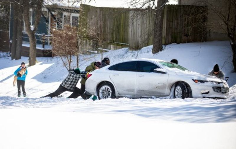 AUSTIN, TX - FEBRUARY 15: East Austin residents push a car out of the snow on February 15, 2021 in Austin, Texas. Winter storm Uri has brought historic cold weather to Texas, causing traffic delays and power outages, and storms have swept across 26 states with a mix of freezing temperatures and precipitation.   Montinique Monroe/Getty Images/AFP (Photo by Montinique Monroe / GETTY IMAGES NORTH AMERICA / AFP)