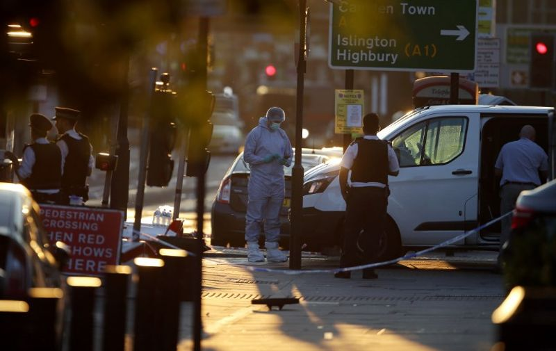 """Forensic investigators work the scene in the Finsbury Park area of north London after a vehichle hit pedestrians, on June 19, 2017.  One man was killed and eight people hospitalised when a van ran into pedestrians near a mosque in north London in an incident that is being investigated by counter-terrorism officers, police said on Monday. The 48-year-old male driver of the van """"was found detained by members of the public at the scene and then arrested by police,"""" a police statement said.  / AFP PHOTO / Daniel LEAL-OLIVAS"""